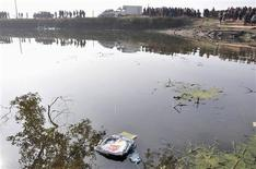 A backpack floats on water after a school van carrying 15 children fell into a pond in Guixi, Jiangxi province, December 24, 2012. REUTERS/Stringer
