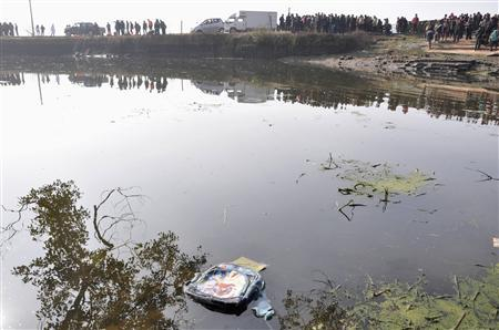 A backpack floats on water after a school van carrying 15 children fell into a pond in Guixi, Jiangxi province, December 24, 2012. The accident killed 11 kindergarten children, local media reported. REUTERS/Stringer
