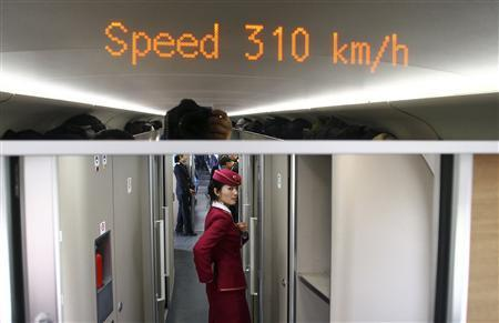 An attendant stands inside a high-speed train during an organized experience trip from Beijing to Zhengzhou, as part of a new rail line, December 22, 2012. REUTERS/China Daily
