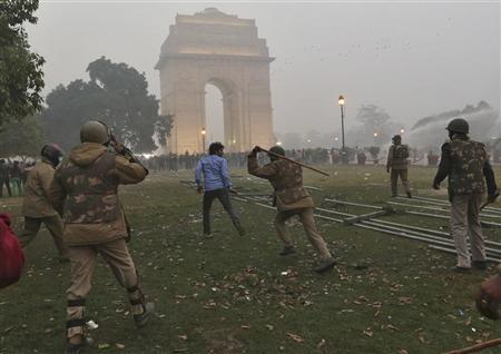 A policeman uses a baton to disperse a demonstrator during a protest in front of India Gate in New Delhi December 23, 2012. REUTERS/Ahmad Masood