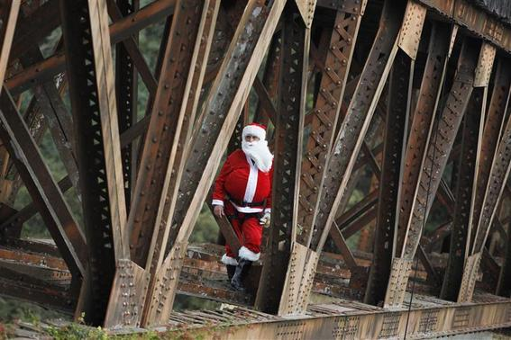 Guatemalan Firefighter Hector Chacon, dressed as Santa Claus, stands before rappelling down from the Belize bridge to give toys to children living in the area under the bridge, Guatemala City December 23, 2012. According the Guatemalan firefighters, they have been giving toys to the children living in the neighborhoods under the Belize bridge, a very poor area of the city, dressed as Santa Claus for 15 years. REUTERS/Jorge Dan Lopez