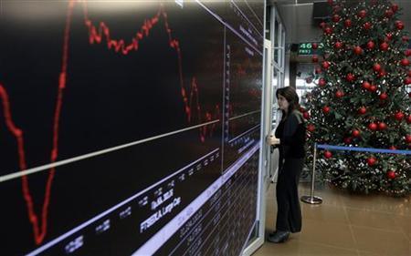 A woman stands next to an electronic board at the reception hall of the Athens stock exchange December 12, 2012. REUTERS/John Kolesidis