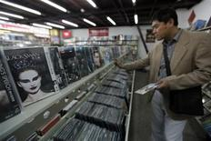 A customer selects pirated DVDs at a store selling pirated CDs and DVDs in Beijing, April 21, 2011. REUTERS/ Jason Lee