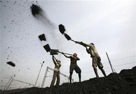 Labourers load coal on trucks at Bari Brahamina on the outskirts of Jammu March 16, 2012. REUTERS/Mukesh Gupta