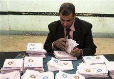 Jueces egipcios estaban investigando el lunes la denuncias de la oposición de supuestas irregularidades antes de anunciar el resultado del referendo que mostraría que la controvertida nueva Constitución fue respaldada por la mayoría de la población. En la imagen del 22 de diciembre, un funcionario recuenta papeletas en un centro electoral en Bani Sweif, a unos 115 km al sur de El Cairo. REUTERS/Stringer