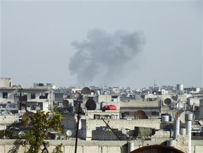 Smoke rises over the city of Homs after an air strike December 24, 2012. REUTERS/Yazan Homsy