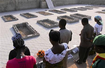 People pray near the graves of victims of a suicide bomb attack during a memorial service at St. Theresa's Church in Madalla, on the outskirts of Nigeria's capital Abuja, December 23, 2012. REUTERS/Afolabi Sotunde