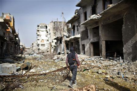 A fighter from the Islamist Syrian rebel group Jabhat al-Nusra walks among damaged houses in Aleppo December 24, 2012. REUTERS/Ahmed Jadallah