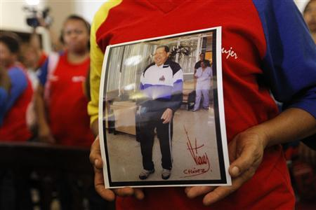 A supporter of Venezuelan President Hugo Chavez holds a picture of him, as she attends a mass to pray for Chavez's health in Caracas December 24, 2012. REUTERS/Carlos Garcia Rawlins