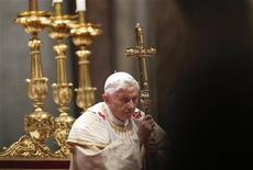 Pope Benedict XVI holds a cross as he leads the Christmas night mass in the Saint Peter's Basilica at the Vatican December 24, 2012. REUTERS/Max Rossi