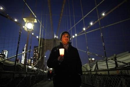 A man takes part in a march across the Brooklyn Bridge in a candlelight vigil aimed at gun control laws, in New York December 23, 2012. REUTERS/Eduardo Munoz