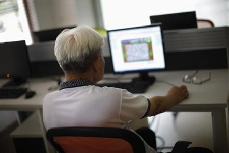 A man sits in front of a computer at a care center in Shanghai September 14, 2012. REUTERS/Carlos Barria/Files
