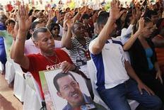 El presidente de Venezuela, Hugo Chávez, experimenta una leve mejoría en su salud, dijo el lunes el Gobierno, casi dos semanas después de someterse a una delicada intervención quirúrgica para tratar el cáncer que padece y que amenaza con alejarlo del poder. En la imagen del 19 de diciembre se puede ver a unos simpatizantes de Chávez en una misa por su salud celebrada en Caracas. REUTERS/Carlos Garcia Rawlins