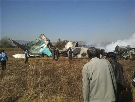 People gather at the wreckage of a Air Bagan Fokker-100 passenger jet that crashed in Heho December 25, 2012. REUTERS/Stringer