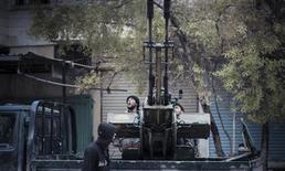 Free Syrian Army fighters fire an anti-aircraft artillery weapon during an air strike in Binsh near Idlib December 23, 2012. REUTERS/Muhammad Najdet Qadour/Shaam News Network/Handout