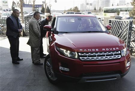 Customers look at a Range Rover Evoque car outside a dealership in Beijing February 17, 2012. REUTERS/Jason Lee