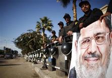 Policiers égyptiens devant la Cour constitutionnelle à côté d'un portrait du président Mohamed Morsi, au Caire. Avec la proclamation officielle des résultats du référendum sur la Constitution, le pouvoir égyptien espère clore mardi des mois de troubles politiques afin de s'attaquer aux graves difficultés économiques du pays. /Photo prise le 23 décembre 2012/REUTERS/Khaled Abdullah