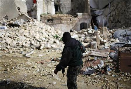 A fighter from Islamist Syrian rebel group Jabhat al-Nusra walks between damaged houses in Aleppo December 24, 2012. REUTERS/Ahmed Jadallah