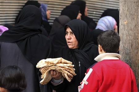 A woman carries bread in Aleppo December 25, 2012. REUTERS/Muzaffar Salman