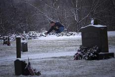 Homem toca neve que cobre o túmulo de Ana Grace Marquez-Greene, de seis anos, vítima do massacre em uma escola infantil na cidade de Newtown, nos EUA. 25/12/2012 REUTERS/Adrees Latif