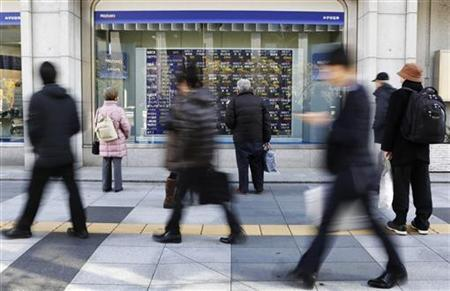 People look at a stock quotation board outside a brokerage in a business district in Tokyo December 19, 2012. REUTERS/Toru Hanai