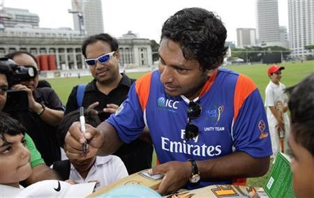Sri Lankan cricketer Kumar Sangakkara (C) signs autographs for fans at the Singapore Cricket Club October 13, 2012. REUTERS/Tim Chong/Files
