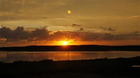 The sun rises over Kawainui marsh on Marine Corps Base Hawaii near where U.S President Barack Obama is staying during his Christmas vacation in Kailua, Hawaii December 24, 2012. REUTERS/Hugh Gentry