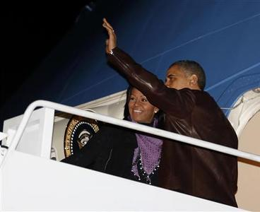 U.S. President Barack Obama waves next to first lady Michelle Obama as they prepare to depart Joint Base Andrews outside Washington, for their holiday trip to Hawaii, December 21, 2012. REUTERS/Larry Downing