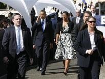 """Barack Obama, ici à Honolulu avec la Prémière dame Michelle Obama, va écourter ses vacances à Hawaï pour tenter de débloquer les négociations entre démocrates et républicains sur le """"mur budgétaire"""" à moins d'une semaine de la date-butoir. /Photo prise le 23 décembre 2012/REUTERS/Hugh Gentry"""