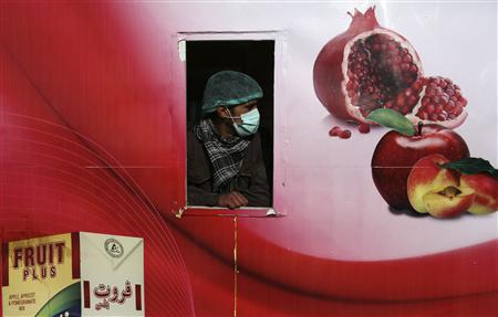 An Afghan worker looks out from a window at a fruit factory which was destroyed by a car suicide bomb attack, in Kabul December 21, 2012. REUTERS/Omar Sobhani