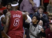LeBron James anotó 29 puntos y flirteó con un triple-doble mientras Miami Heat se impuso por 103-97 a Oklahoma City Thunder en una repetición de la última final de la NBA en uno de los cinco partidos disputados el día de Navidad. En la imagen, LeBron James saluda a la artista Gladys Knight tras el partido en Miami, el 25 de diciembre de 2012. REUTERS/Rhona Wise