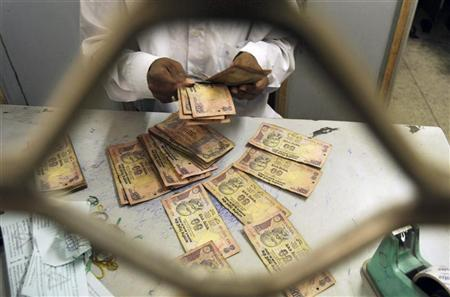 An employee sorts rupee notes at a cash counter inside a bank in the northeastern Indian city of Agartala February 18, 2010. REUTERS/Jayanta Dey/Files