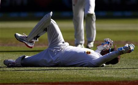 Sri Lanka's wicketkeeper Kumar Sangakkara lies on the ground after dropping a catch from Australia's Shane Watson during the first day of the second cricket test at the Melbourne Cricket Ground December 26, 2012. REUTERS/David Gray