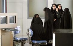 Иранские полицейские стоят возле пункта досмотра в международном аэропорту имени Имама Хомейни в Тегеране 30 апреля 2005 года. Иранский парламент ввел запрет на полет самолетов во время азана - призыва к молитве, и озаботился соблюдением правил исламского дресс-кода женщинами, работающими в аэропортах и авиакомпаниях, сообщило в среду полугосударственное новостное агентство Mehr. REUTERS/Morteza Nikoubazl