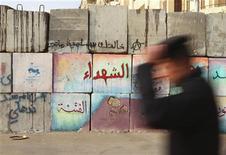 El presidente egipcio, Mohamed Mursi, promulgó una nueva Constitución redactada por islamistas que afirma que ayudará a poner fin a las turbulencias políticas y le permitirá enfocarse en recomponer una economía muy frágil. En la imagen, un policía camina junto a una barrera recién levantada para contener a los manifestantes lejos del palacio presidencial en El Cairo, el 25 de diciembre de 2012. REUTERS/Asmaa Waguih