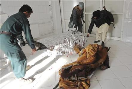 Afghan policemen carry the dead body of a victim at a local hospital after a suicide bomb attack in Khost province December 26, 2012. REUTERS/Anwarullah