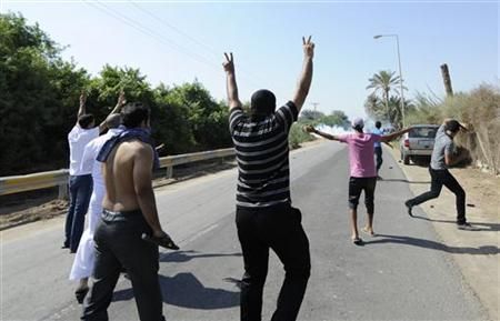 Anti-government protesters gesture as they walk towards riot police (unseen, behind tear gas) blocking a road leading to the village of Diraz, west of Manama November 9, 2012. REUTERS/Stringer