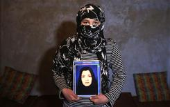 Fatima, 13, holds a picture of her mother Narges Rezaeimomenabad, suspected of killing a U.S. contractor at a police headquarters, at her home in Kabul December 26, 2012. REUTERS/Mohammad Ismail