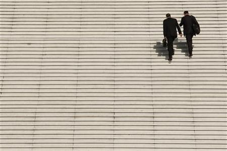 Businessmen climb the steps at the Arche de la Defense, the financial and business district west of Paris, August 5, 2009. REUTERS/Benoit Tessier