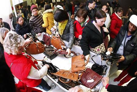 Customers rush to buy purses at the Macy's store during Thanksgiving Day holiday in New York November 23, 2012. REUTERS/Carlo Allegri