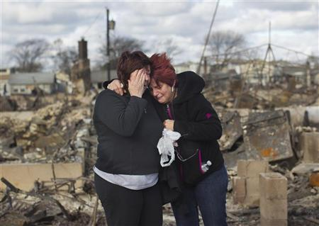 Neighbors Lucille Dwyer (R) and Linda Strong embrace after looking through the wreckage of their homes devastated by fire and the effects of Hurricane Sandy in the Breezy Point section of the Queens borough of New York October 31, 2012. The U.S. Northeast began crawling back to normal on Wednesday after monster storm Sandy crippled transportation, knocked out power for millions and killed at least 45 people in nine states with a massive storm surge and rain that caused epic flooding. REUTERS/Shannon Stapleton