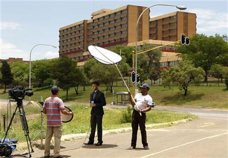 A television crew films outside a military hospital where former South African president Nelson Mandela is hospitalized in Pretoria December 9, 2012. REUTERS/Siphiwe Sibeko