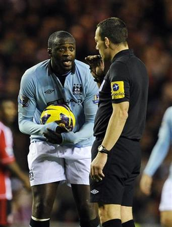Manchester City's Yaya Toure (L) reacts with referee Kevin Friend during their English Premier League soccer match against Sunderland in Sunderland, northern England December 26, 2012. REUTERS/Nigel Roddis