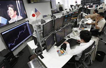 Employees of a foreign exchange trading company look at monitors as a television set shows Japan's incoming Prime Minister and the leader of Liberal Democratic Party (LDP) Shinzo Abe speaking in Tokyo December 26, 2012. REUTERS/Yuriko Nakao