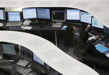 A Tokyo Stock Exchange employee laughs as he works at the bourse in Tokyo December 17, 2012. REUTERS/Yuriko Nakao