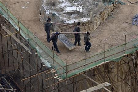 Villagers carry a gravestone of an ancestral tomb away from a construction site of a residential compound in Taiyuan, Shanxi province, December 18, 2012. REUTERS/Stringer