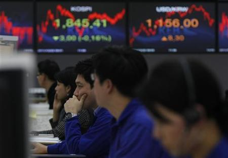 Korea Exchange Bank (KEB) foreign currency dealers work in front of displays showing the current Korea Composite Stock Price Index (KOSPI) and the exchange rate between the South Korean won and the dollar (R) at the bank in Seoul December 22, 2011. REUTERS/Kim Hong-Ji/Files