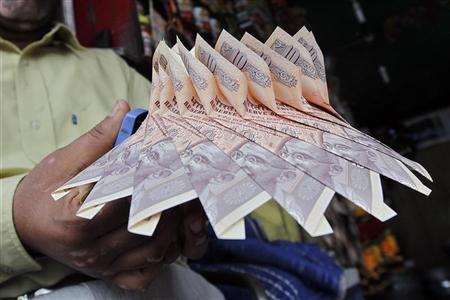 A Kashmiri shopkeeper staples together Indian currency notes to make a garland at a market in Srinagar September 3, 2012. REUTERS/Fayaz Kabli/Files