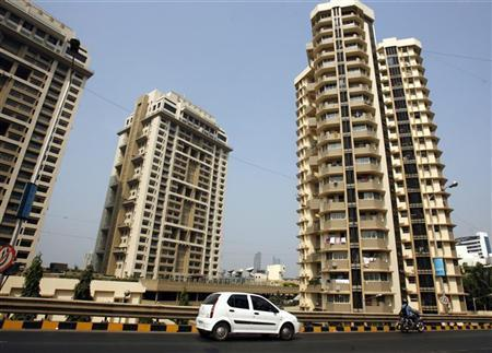 A vehicle drives past residential buildings in India's financial capital Mumbai January 27, 2010. REUTERS/Punit Paranjpe/Files