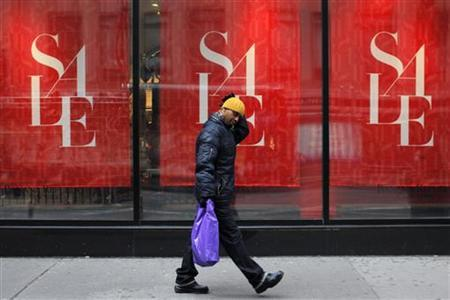 A man walks past a shop while carrying a shopping bag in New York, December 26, 2012. The 2012 holiday season may have been the worst for retailers since the financial crisis, with sales growth far below expectations, forcing many to offer massive post-Christmas discounts in hopes of shedding excess inventory. REUTERS/Eduardo Munoz (UNITED STATES - Tags: BUSINESS)